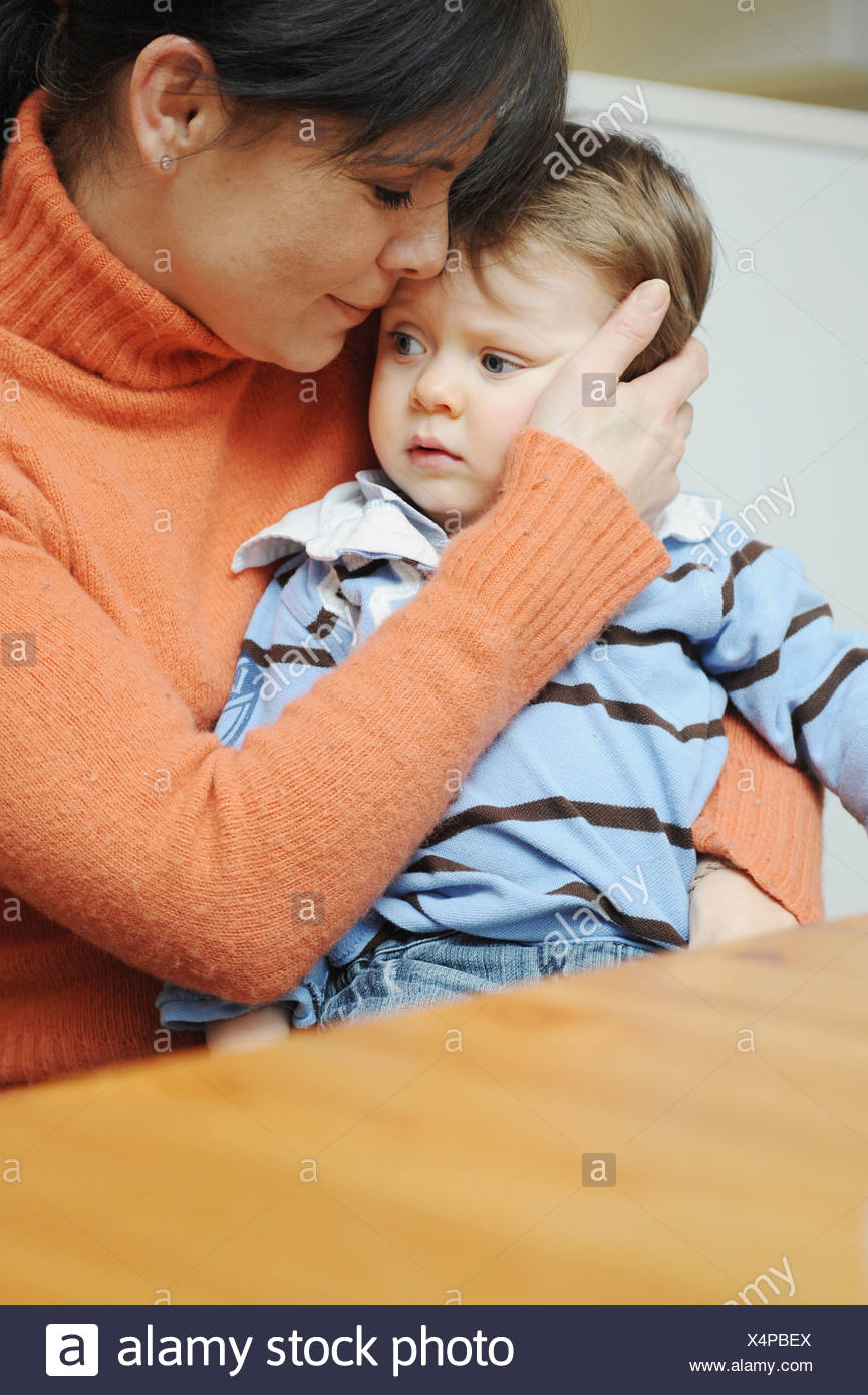 Mother hugging toddler son at table - Stock Image