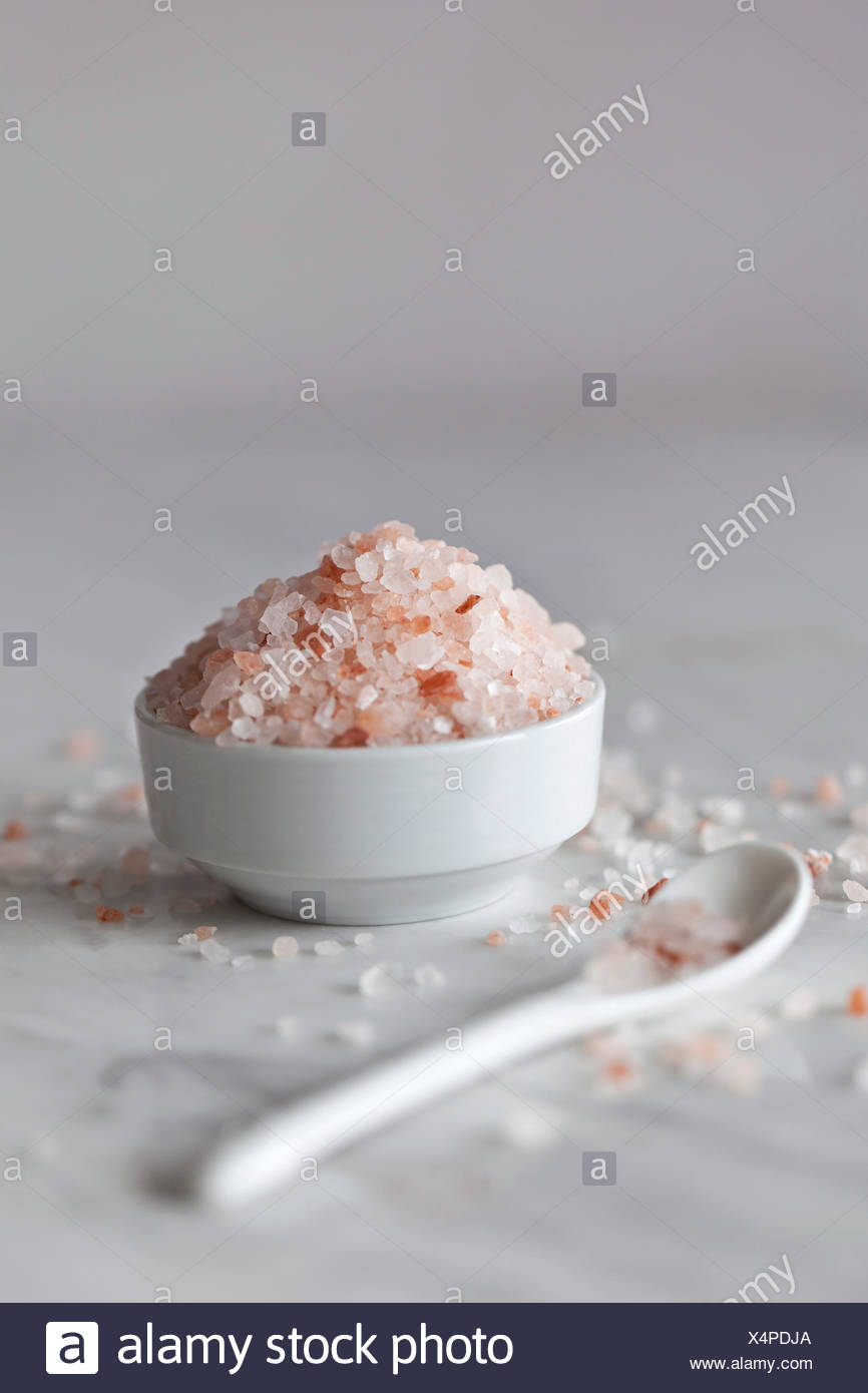 Pink Himalayan salt in the small white bowl and white marble surface - Stock Image