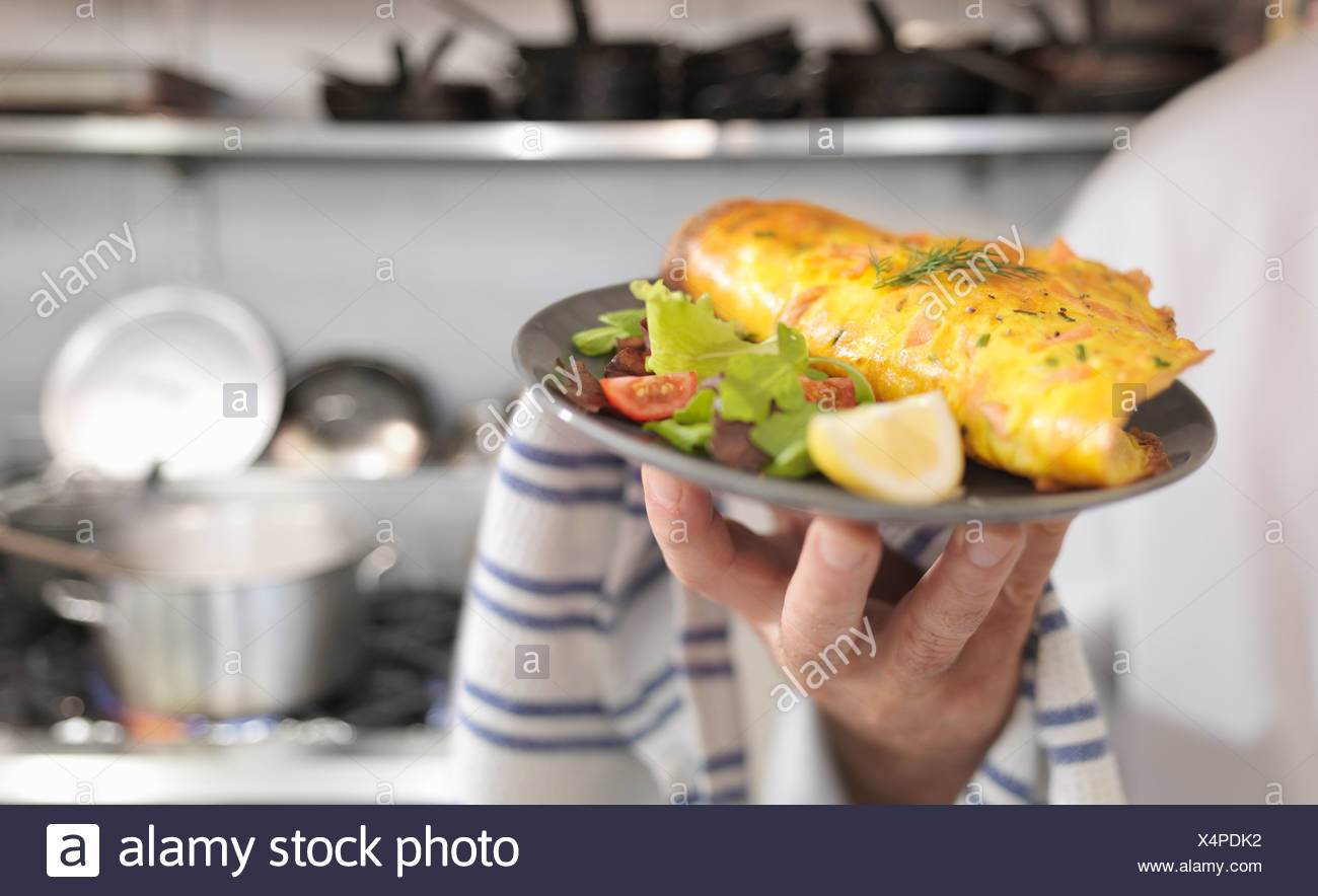 Chef holding salmon omelet and salad Stock Photo