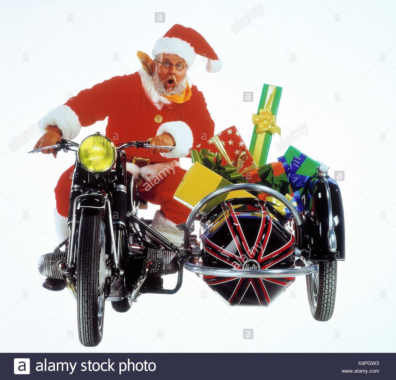 Santa Claus, motorcycle, side car, presents, deliver Christmas, distribution presents, Santa, motorcycle driving, sidecar, Christmas presents, deliver, transport, facial play, fright, studio, cut out - Stock Image