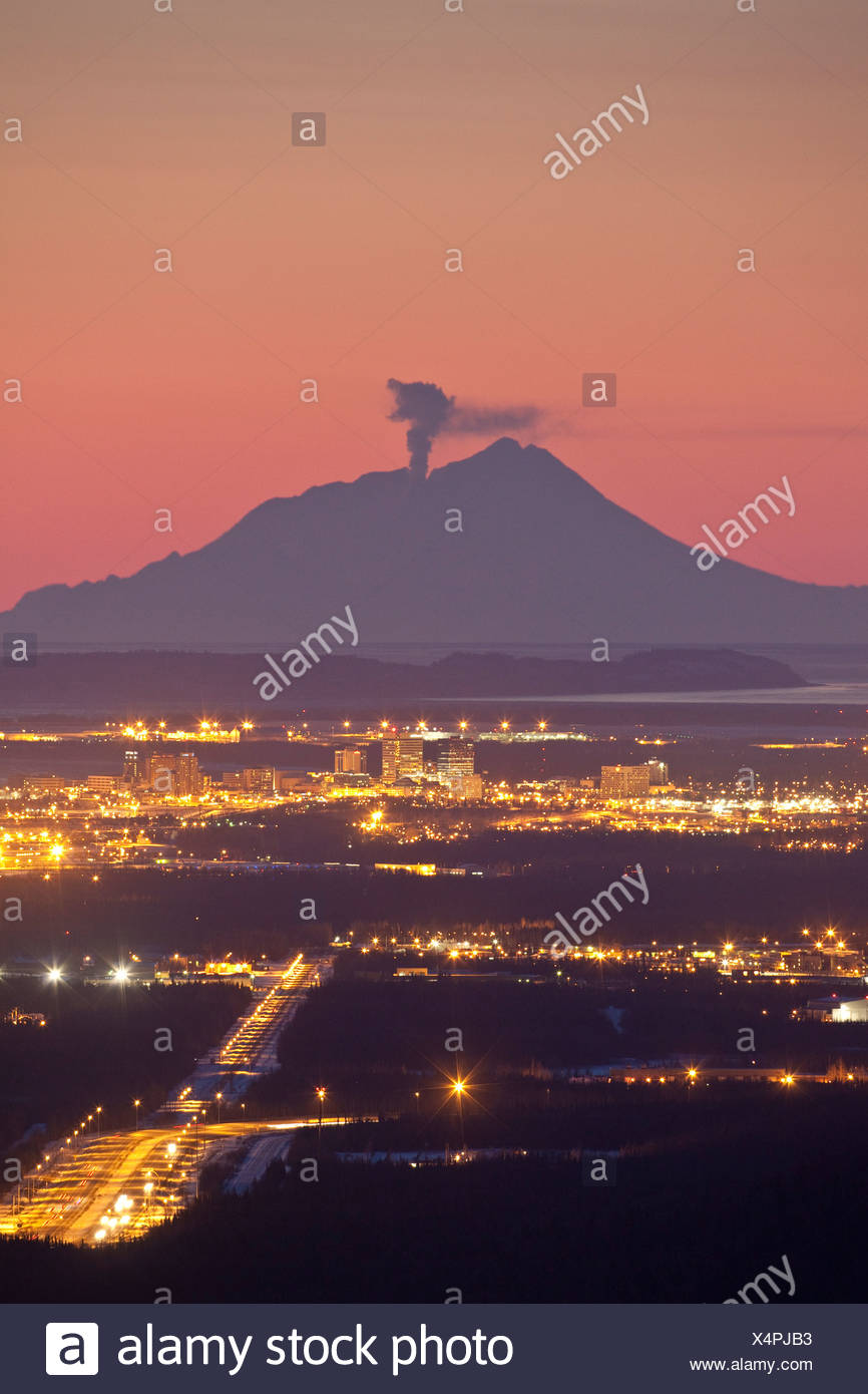View of minor eruption of ash and steam from Mt. Redoubt with Anchorage, Alaska in the foreground during Winter - Stock Image
