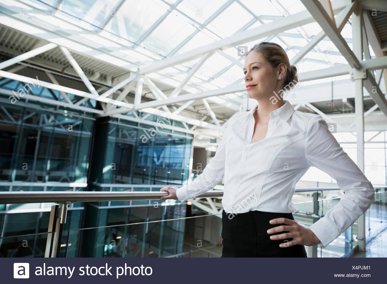 Confident businesswoman looking away in atrium - Stock Image
