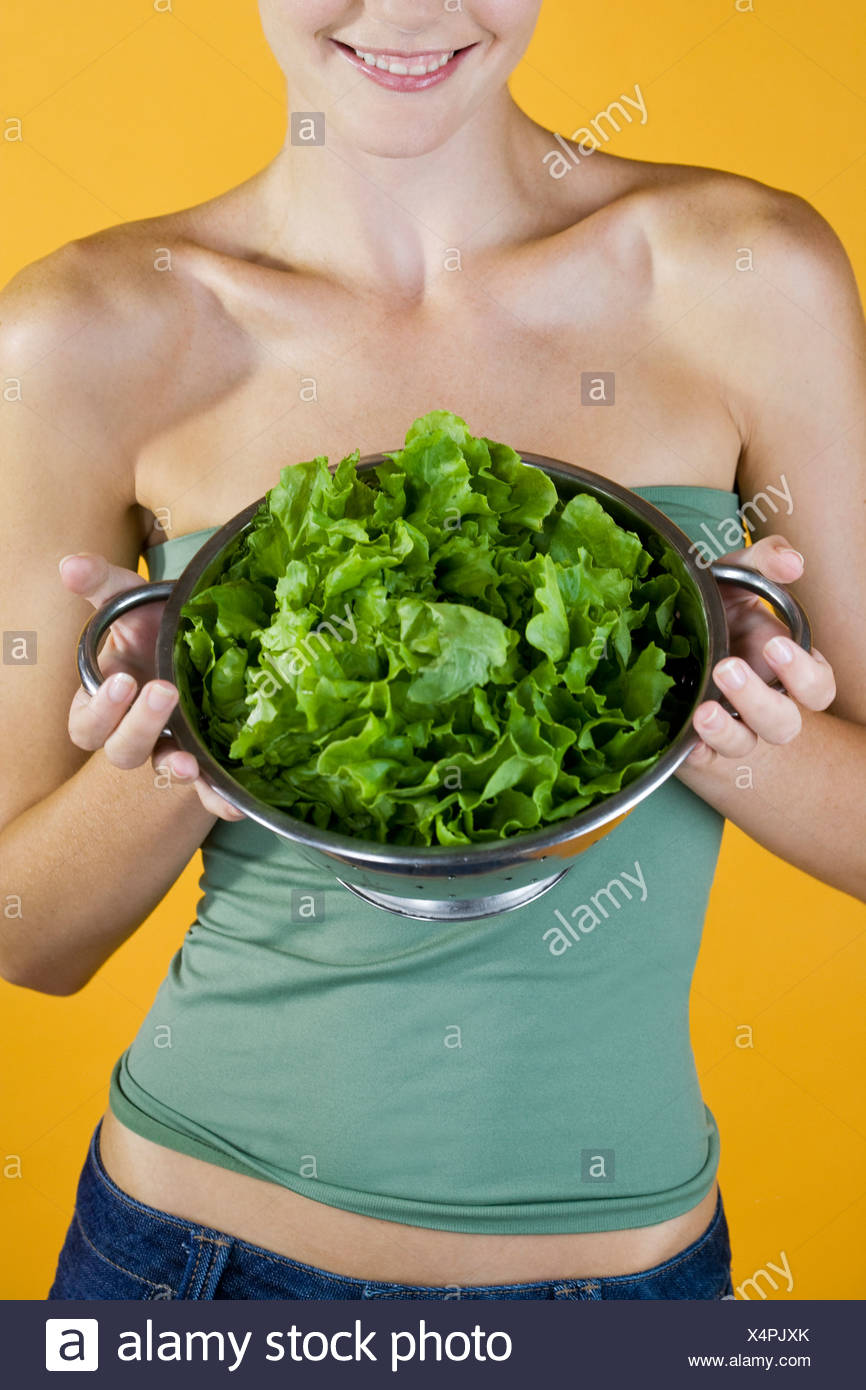 A Young Woman Holding A Colander Full Of Lettuce Stock Photo