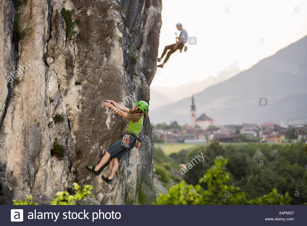 Climber lead climbing on a rock wall, climber abseiling behind, Zirl behind, Martinswand, Tyrol, Austria - Stock Image