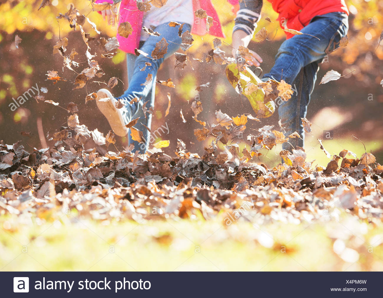 Boy and girl kicking in autumn leaves - Stock Image