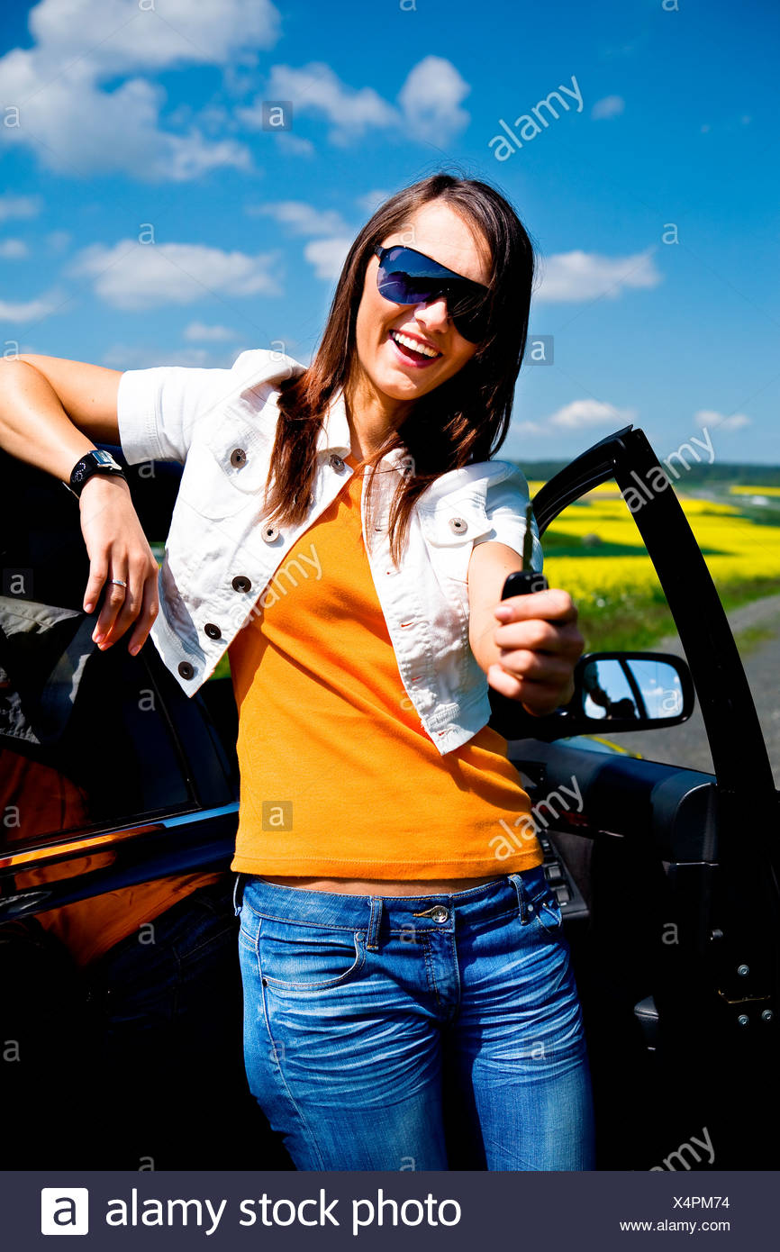 Young woman with her car, thumbs up - Stock Image