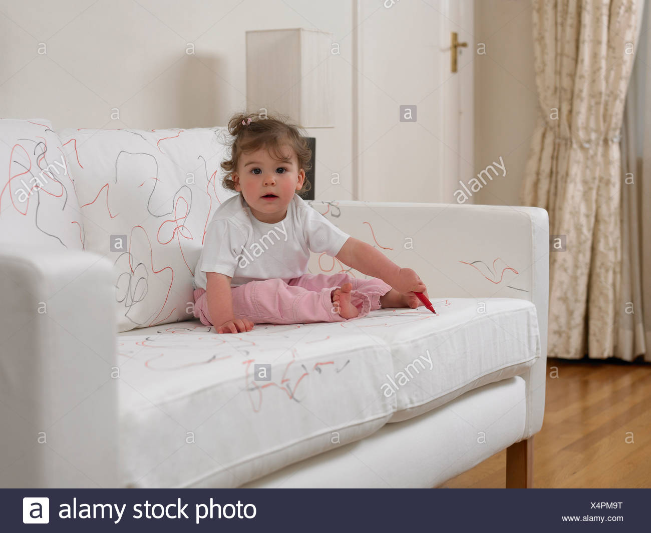 Baby girl using marker on sofa - Stock Image