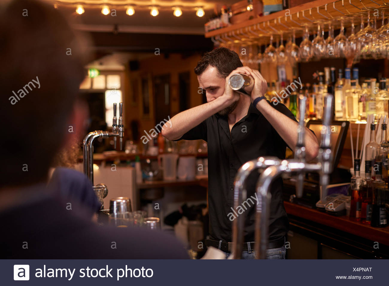Barman Making Cocktail In Bar Using Shaker - Stock Image