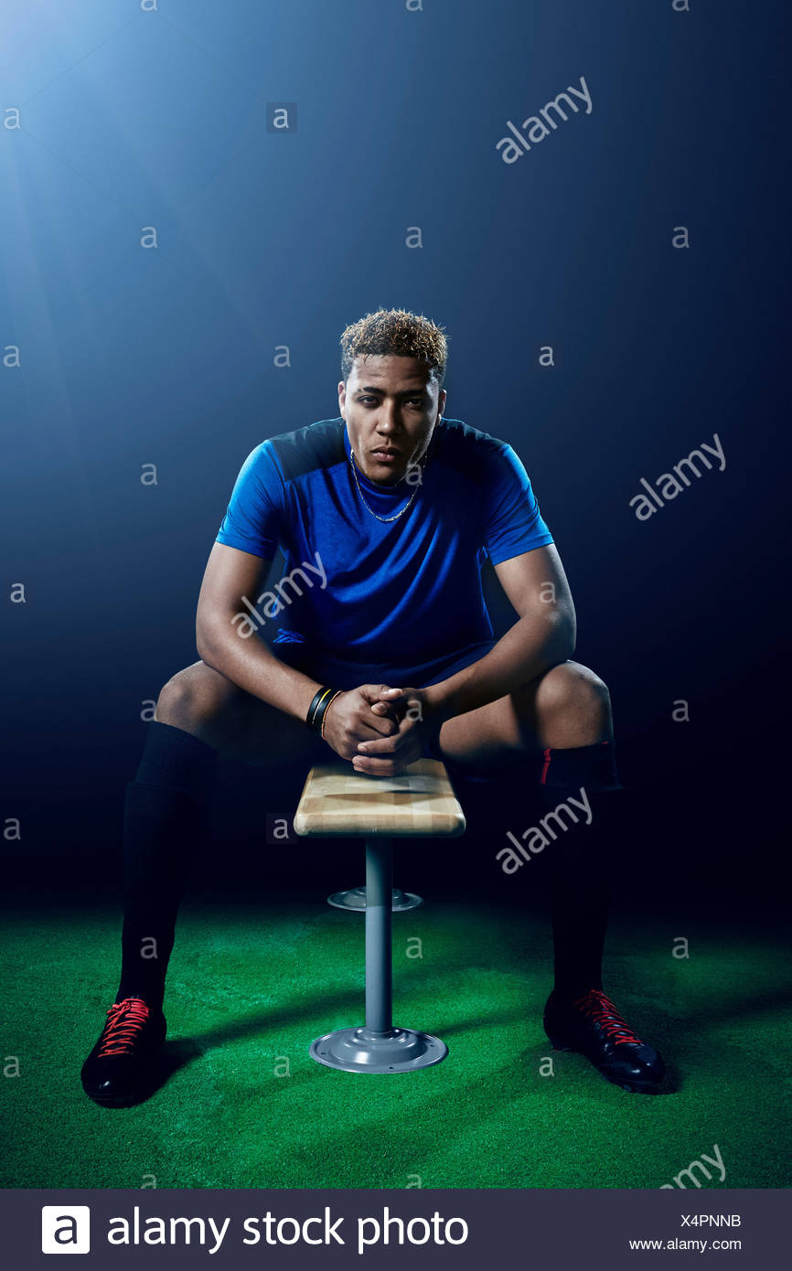 Portrait of young male soccer player on bench - Stock Image