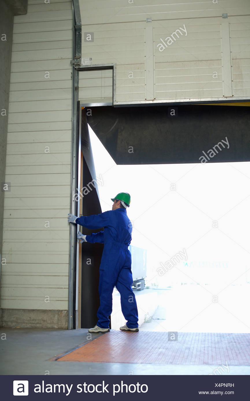 Man standing handling a roller shutter - Stock Image