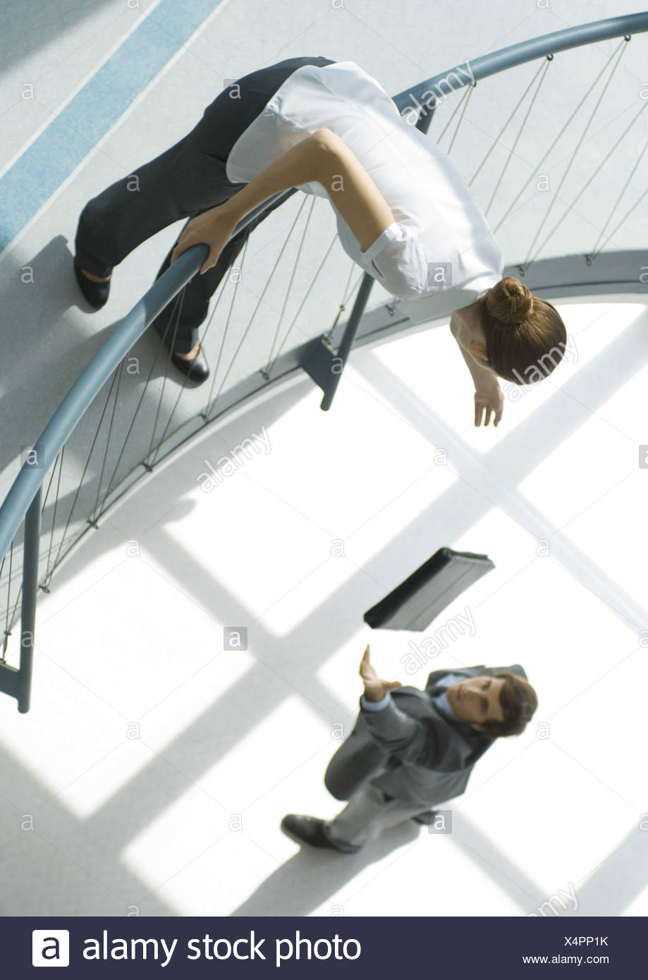 Businessman throwing briefcase up to woman from lower floor, full length, high angle view - Stock Image