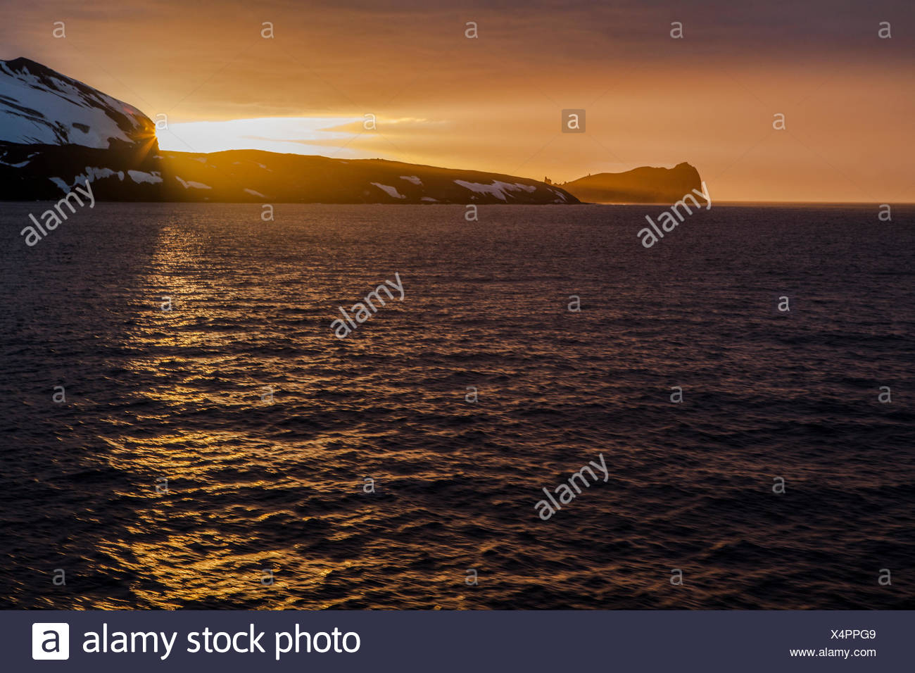 The sun sinks below the horizon at Deception Island. - Stock Image
