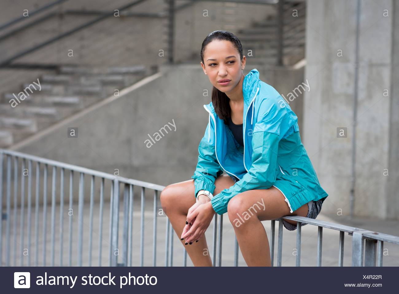 MODEL RELEASED. Portrait of young woman sitting on railings looking away. - Stock Image