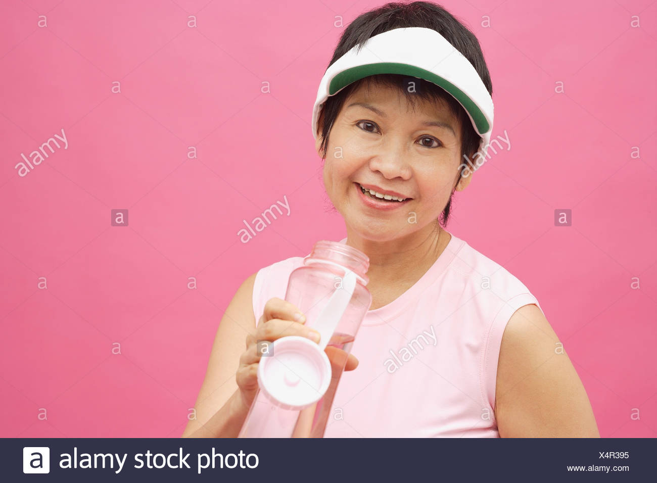 7020df84 Mature woman wearing sun visor and water bottle, smiling Stock Photo ...