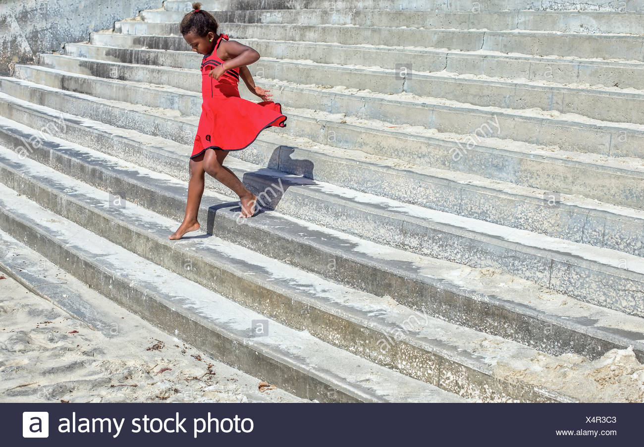 Girl in a red dress running down steps - Stock Image