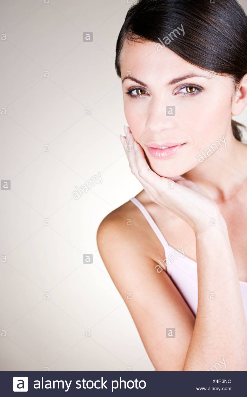 Portrait of a young woman touching her face - Stock Image