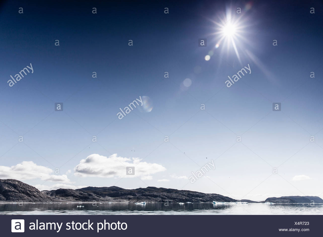View of sea and rocks with sun shines brightly on sunny day - Stock Image
