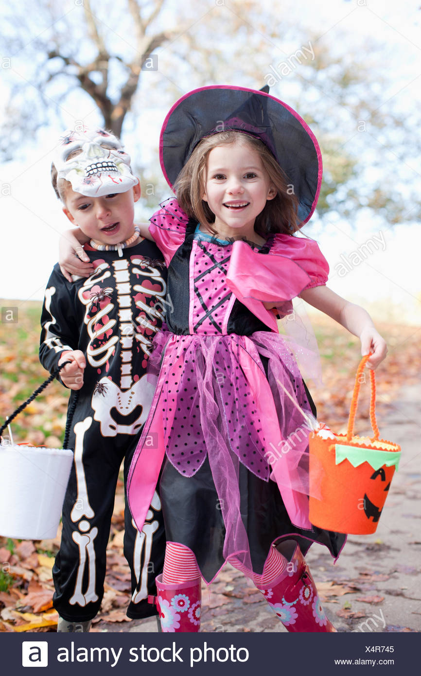 Laughing children in Halloween costumes - Stock Image