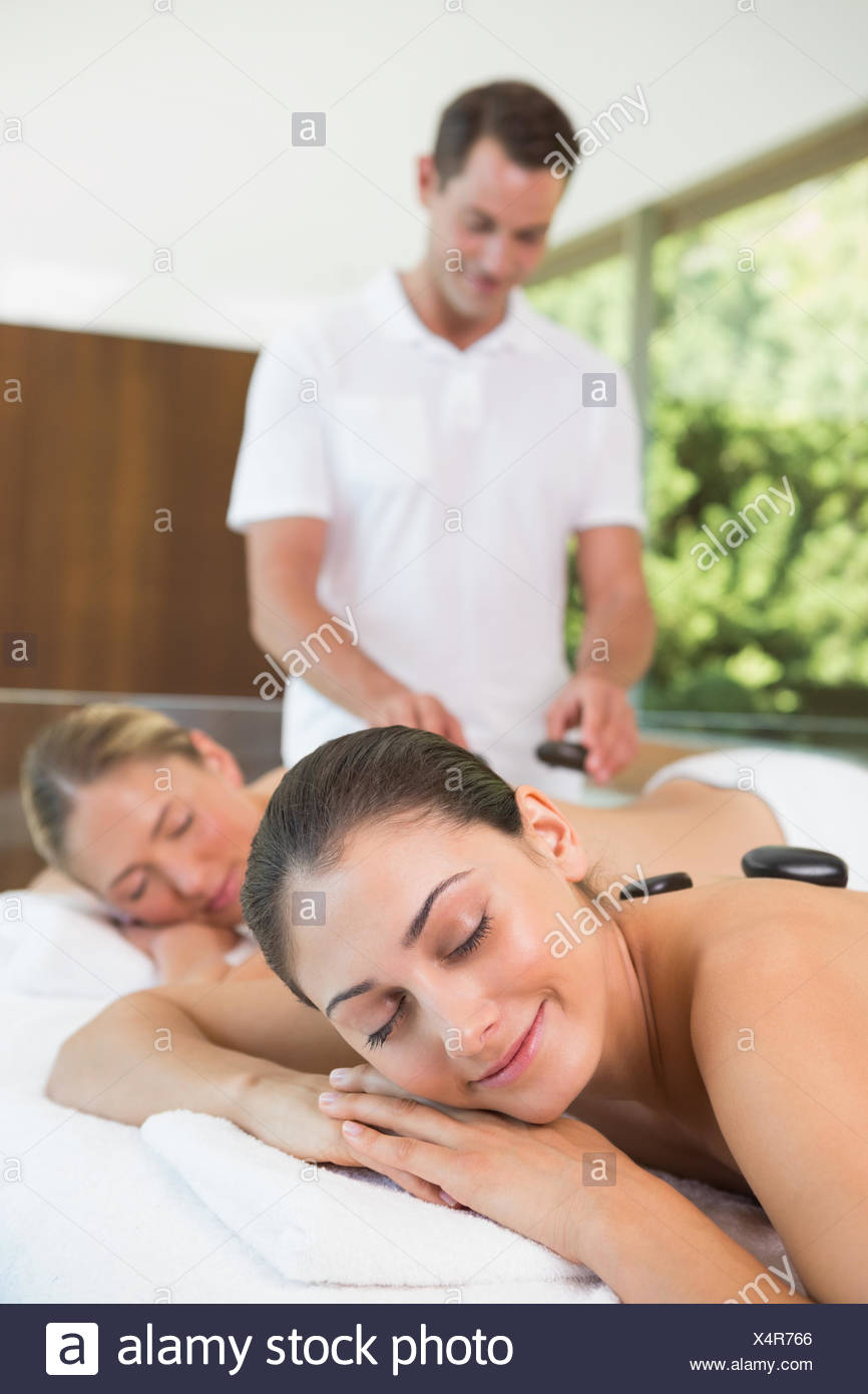 Pretty friends lying on massage tables getting hot stone massages - Stock Image
