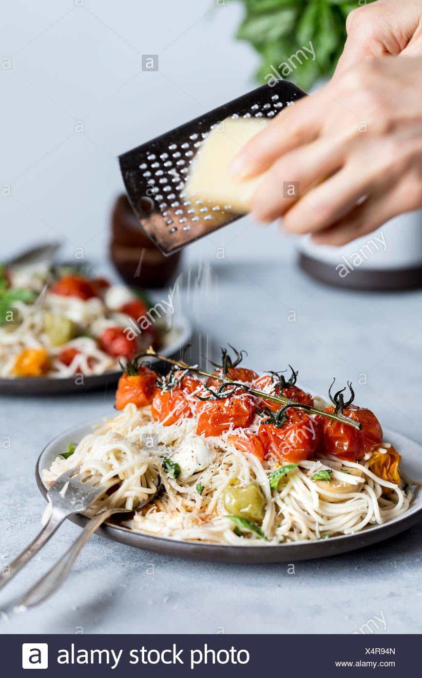 A woman is shredding parmesan cheese onto a bowl of spaghetti topped off with roasted tomatoes, mozarella cheese, and basil. - Stock Image