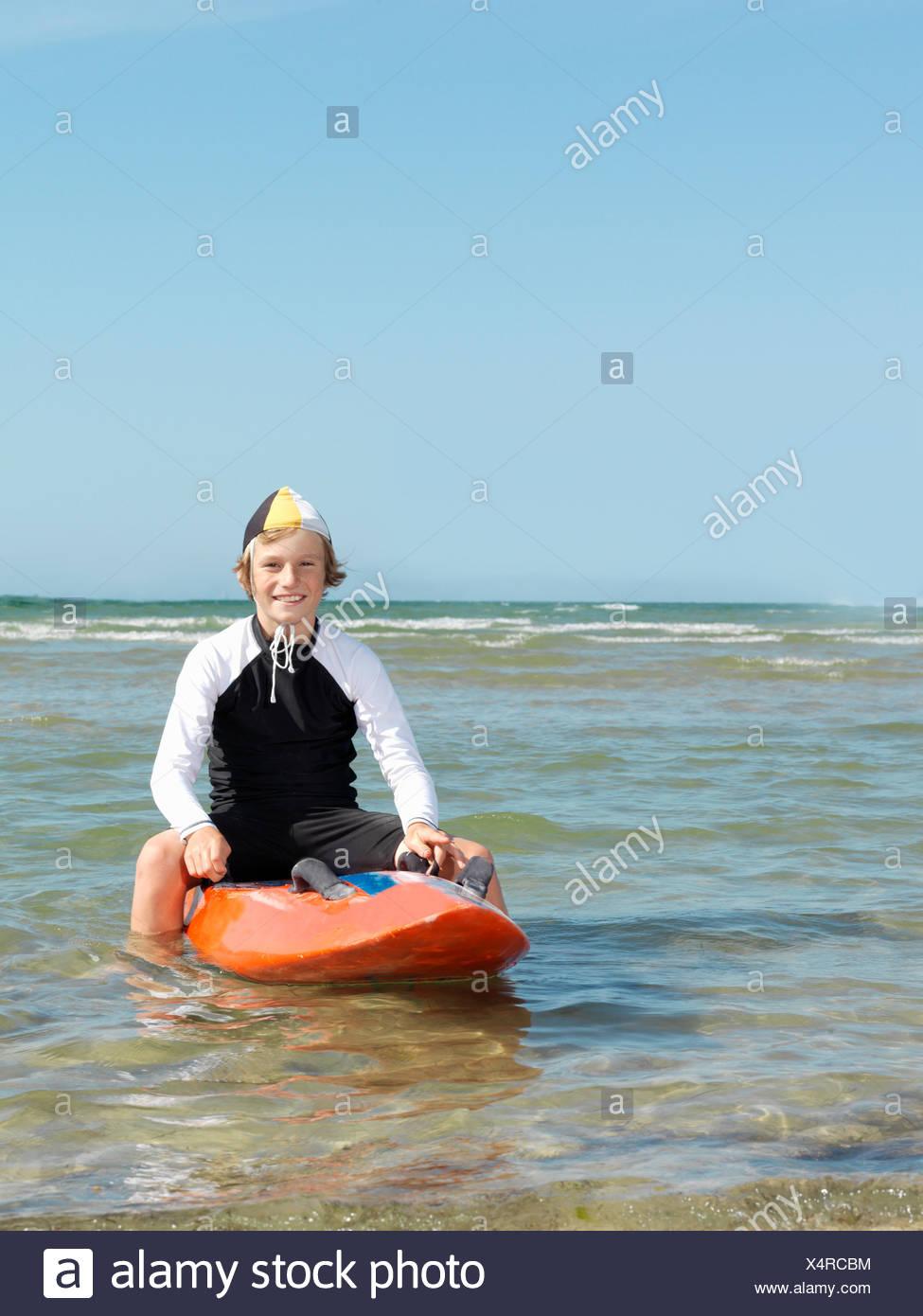 Portrait of boy nipper (child surf life savers) astride surfboard, Altona, Melbourne, Australia - Stock Image