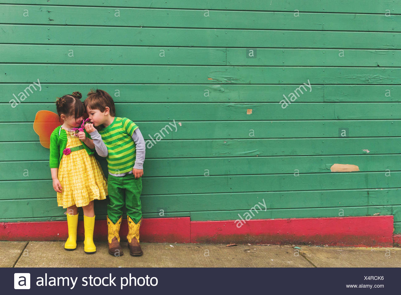 Boy and girl dressed up as a caterpillar and butterfly smelling flowers - Stock Image