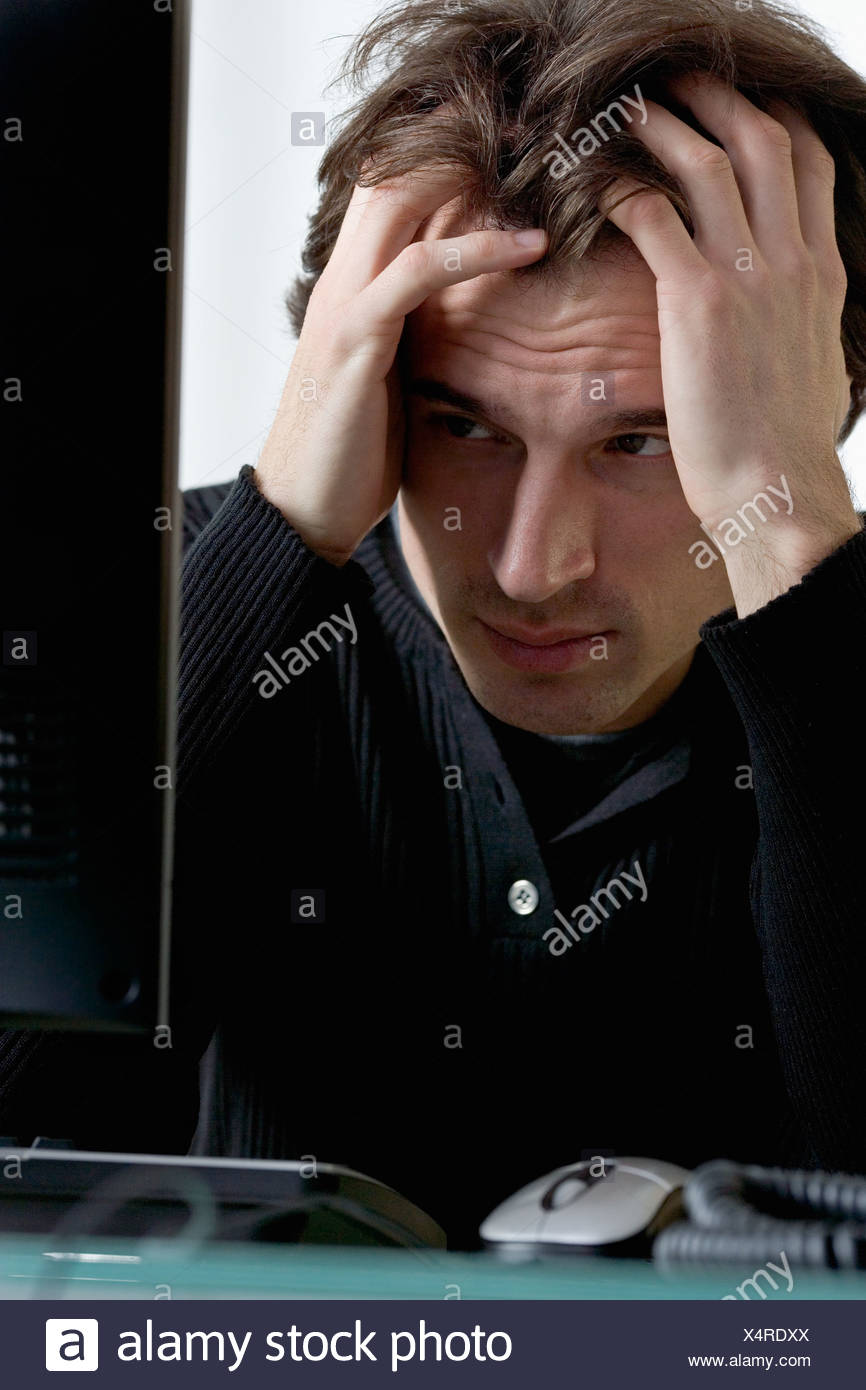 Closeup of distressed man with computer - Stock Image
