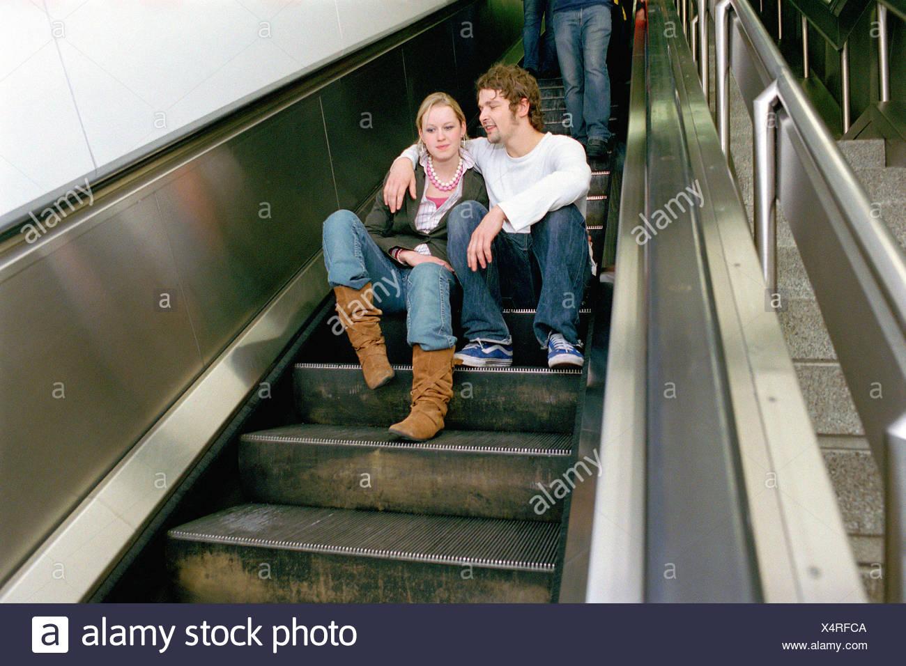 Couple sitting on escalator Stock Photo