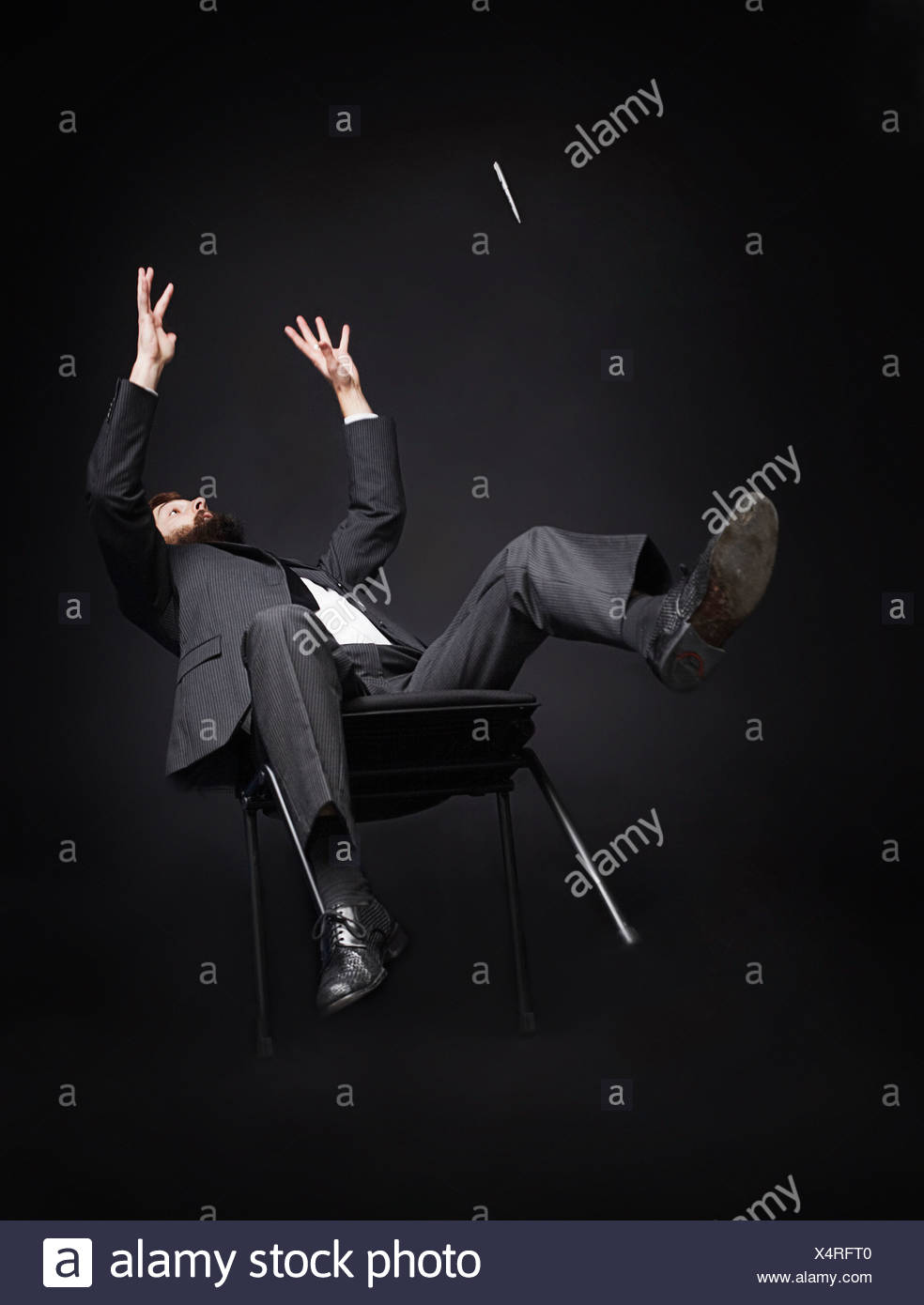 Man falling off a chair - Stock Image