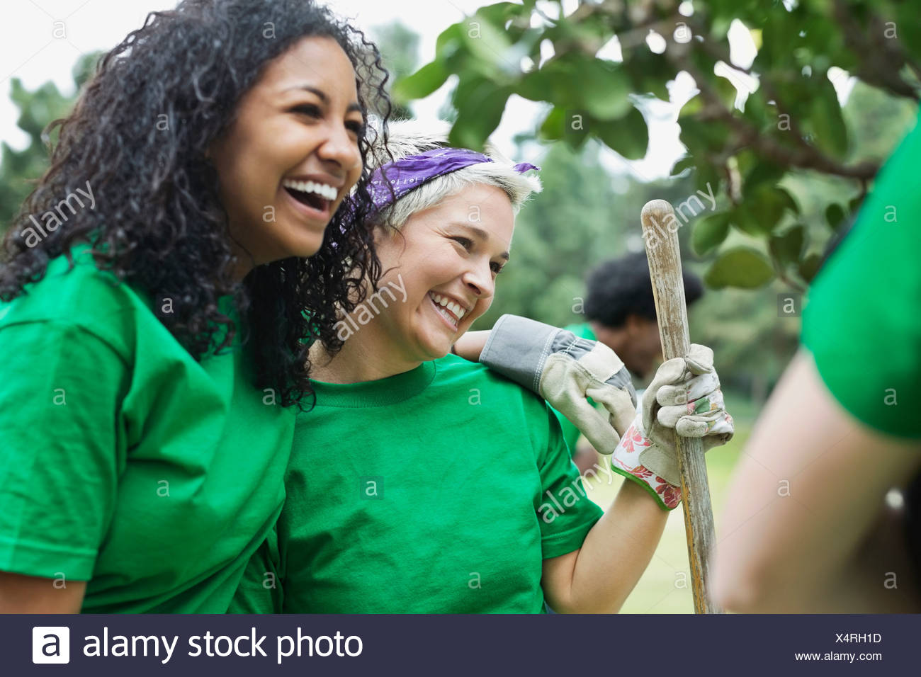 Happy young female environmentalist with friend holding shovel in park - Stock Image