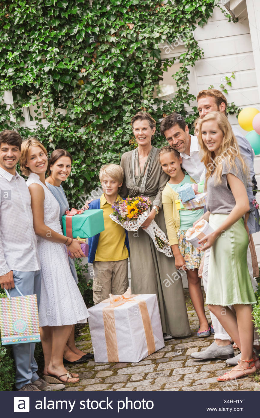 Portrait of three generation family in garden with bouquet and birthday gifts - Stock Image