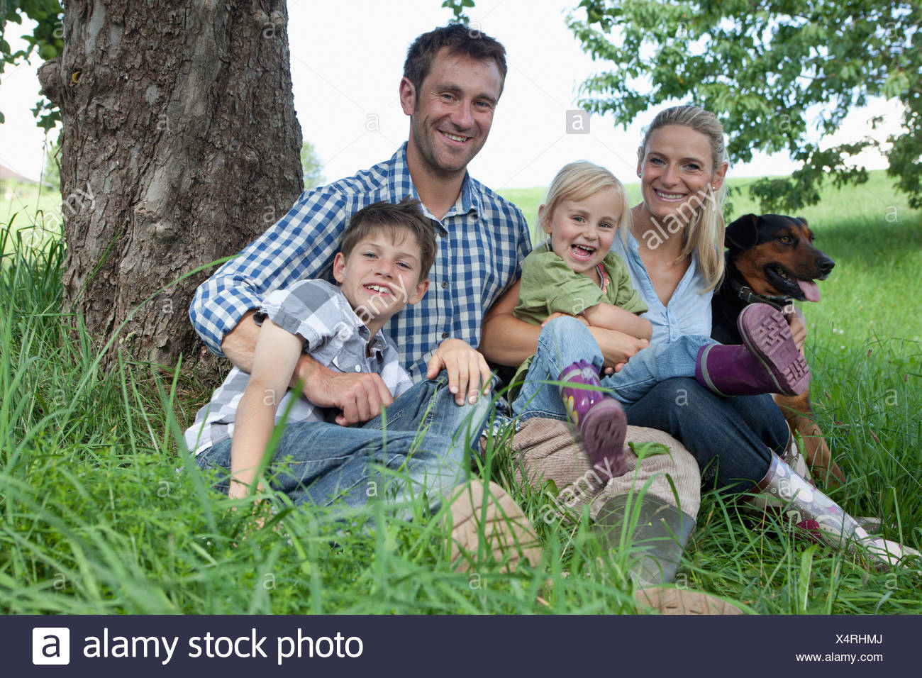 Germany, Bavaria, Altenthann, Family with dog under tree, smiling, portrait - Stock Image