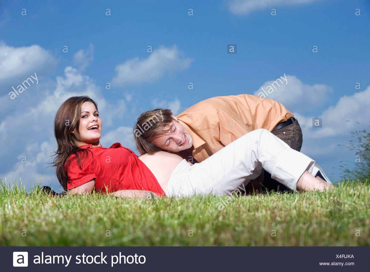 Woman lying in meadow, man with head on pregnant woman's belly, portrait - Stock Image