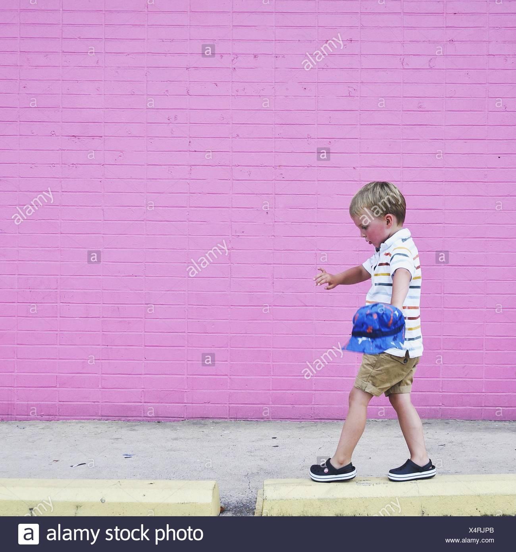 Boy walking on raised sidewalk - Stock Image