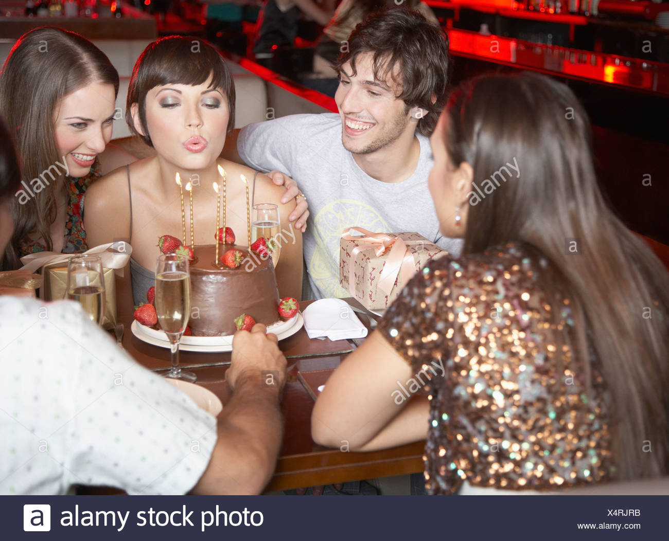 five people having fun and smiling at a birthday party in a restaurant - Stock Image