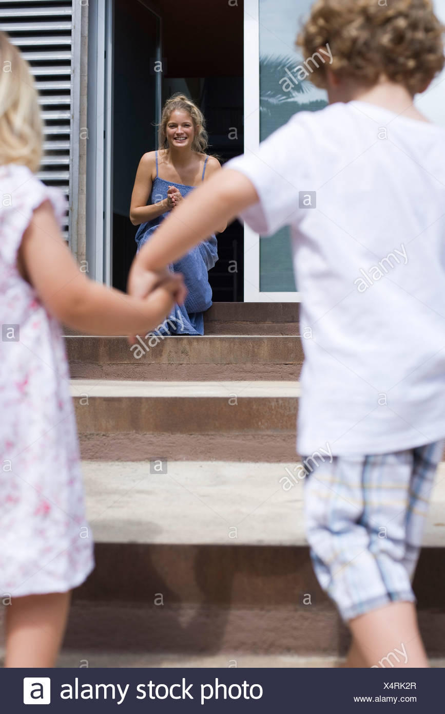 Young siblings holding hands, running toward mother Stock Photo