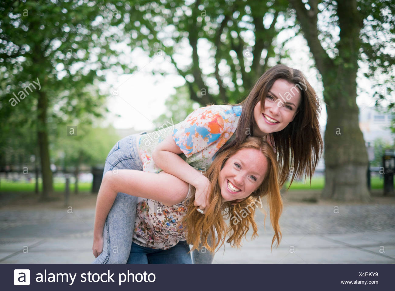 Portrait of two young female best friends giving piggy back in park - Stock Image