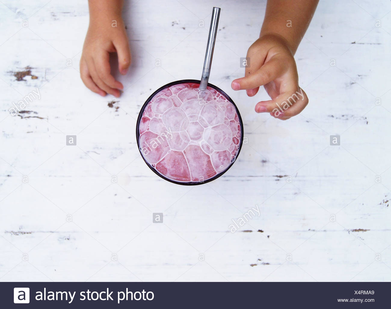 Child's hands reaching for a strawberry milkshake with bubbles - Stock Image