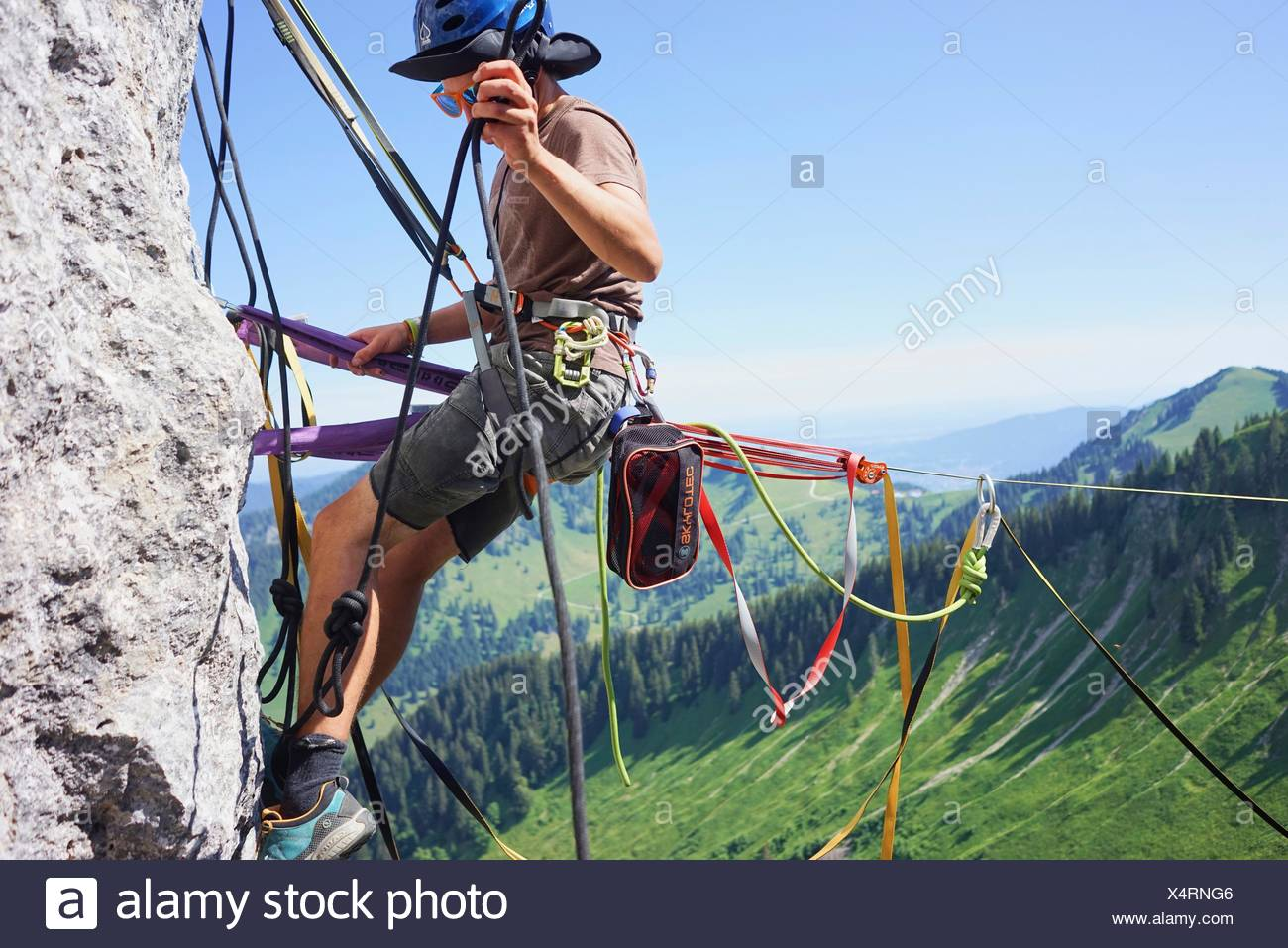 man at anchor point of highline slackline, checking safeguard, in Bavarian alps, near mountain Blankenstein, south of Germany - Stock Image
