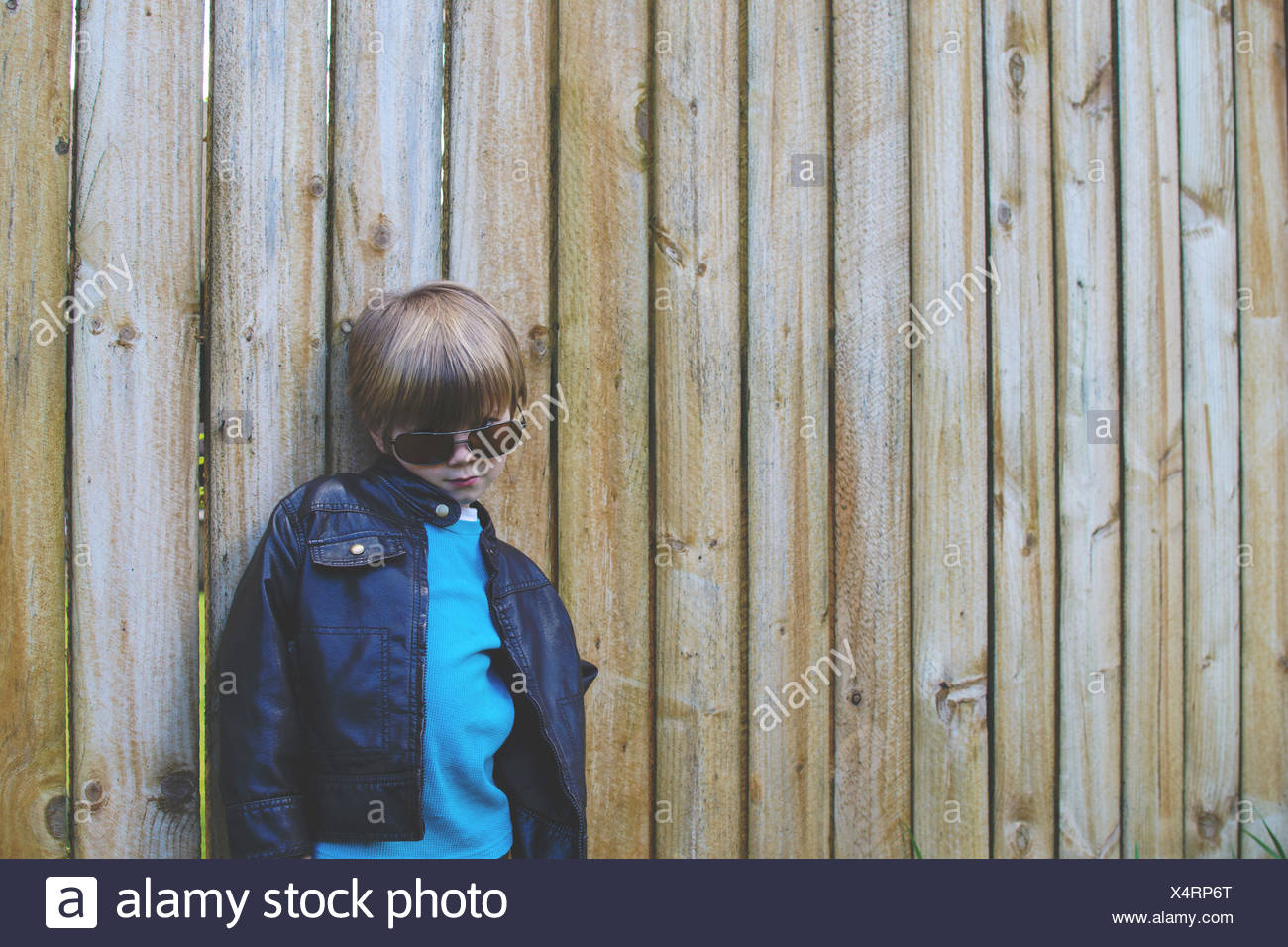Boy standing against fence (4-5 years) - Stock Image
