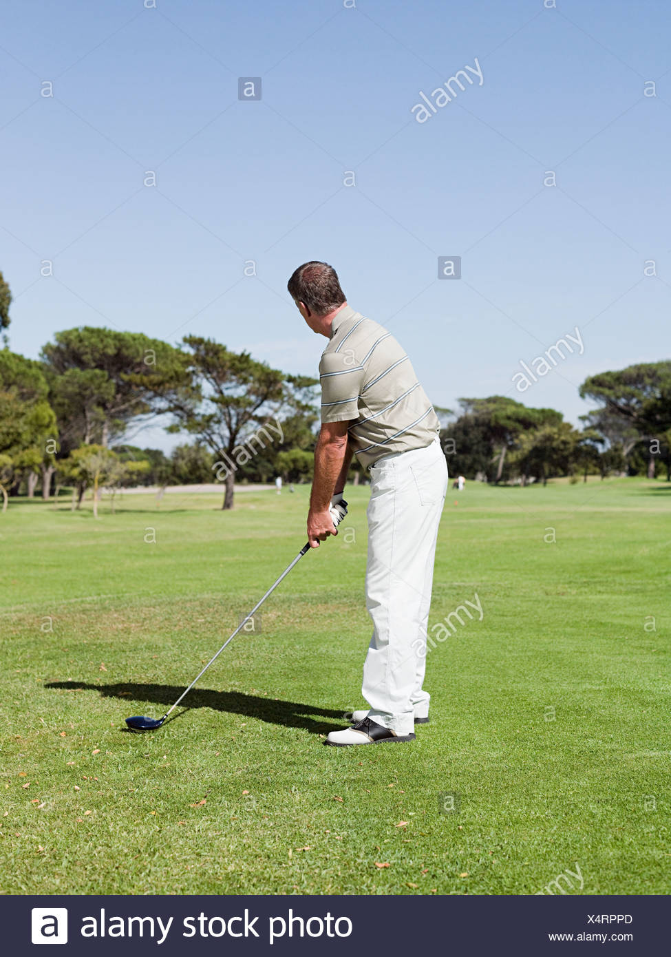 Man playing golf on golf course - Stock Image