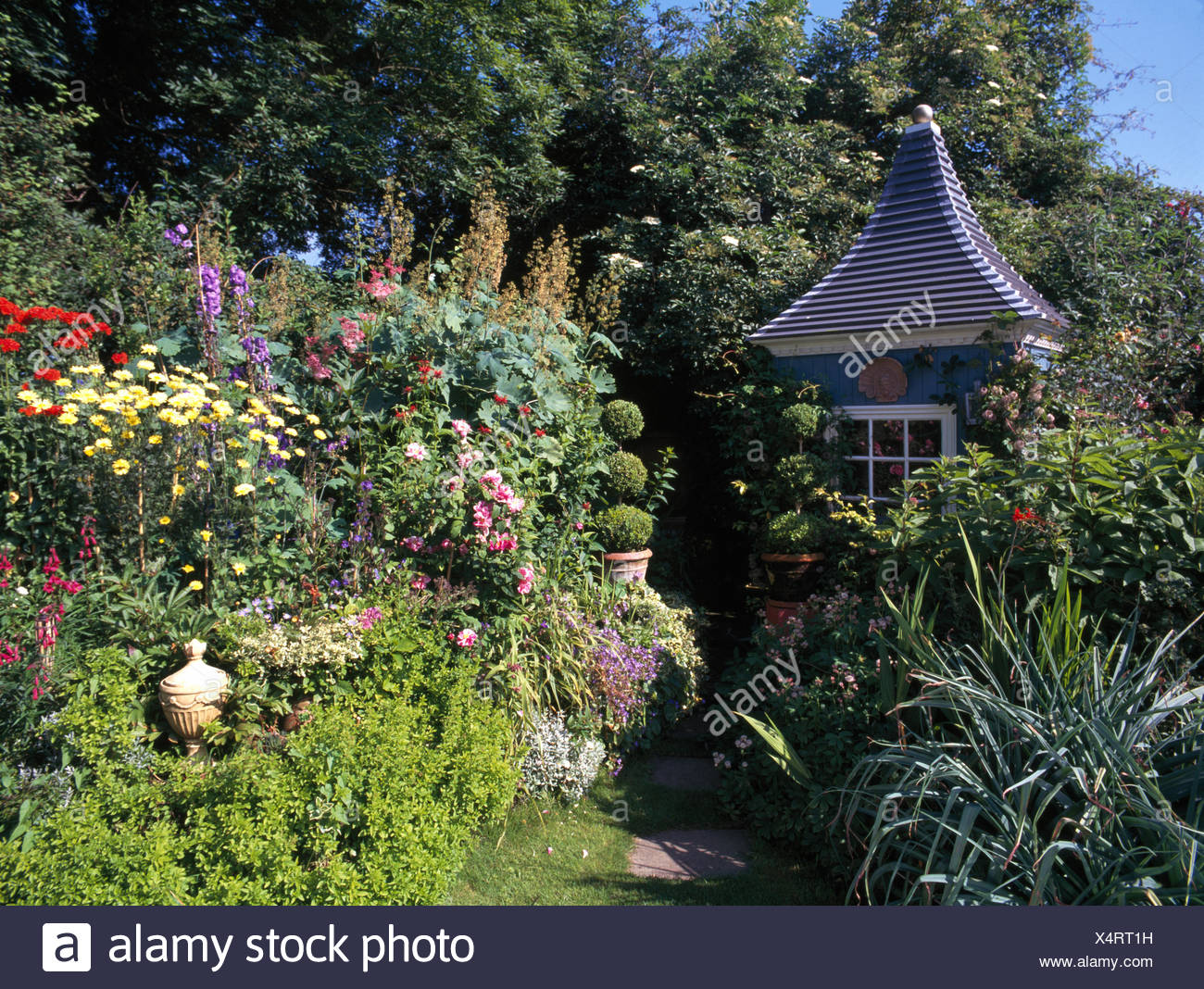 Colorful perennials in border of country garden with elegant gazebo ...