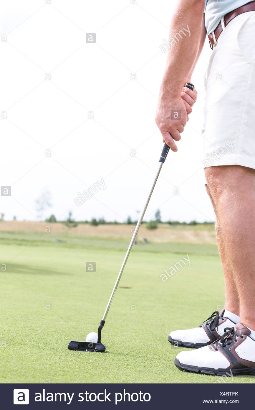 Low section of mid-adult man playing golf against clear sky - Stock Image