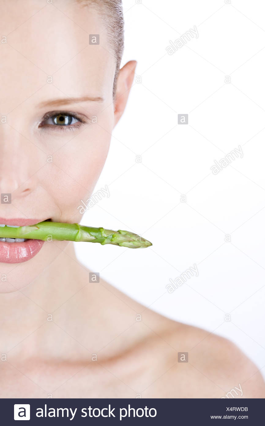 A young woman with a piece of asparagus in between her teeth, right side - Stock Image