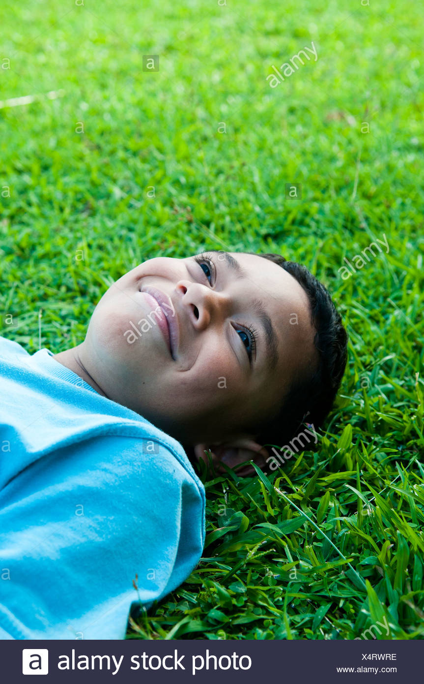 Boy laying in grass smiling, Cook Islands. - Stock Image