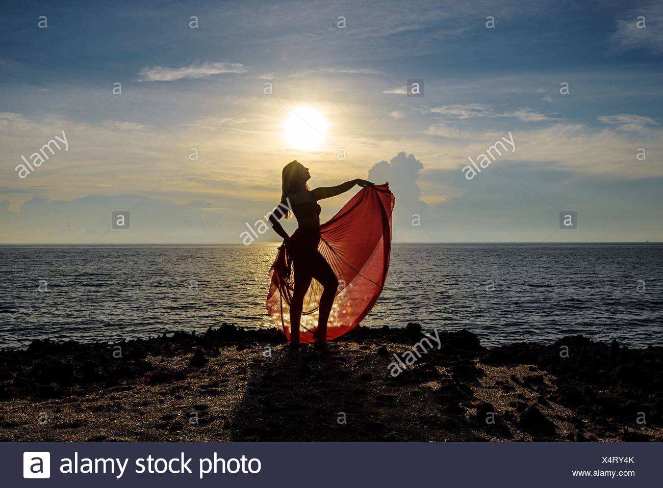 Woman Standing On Cliff By Sea Against Sky During Sunset - Stock Image