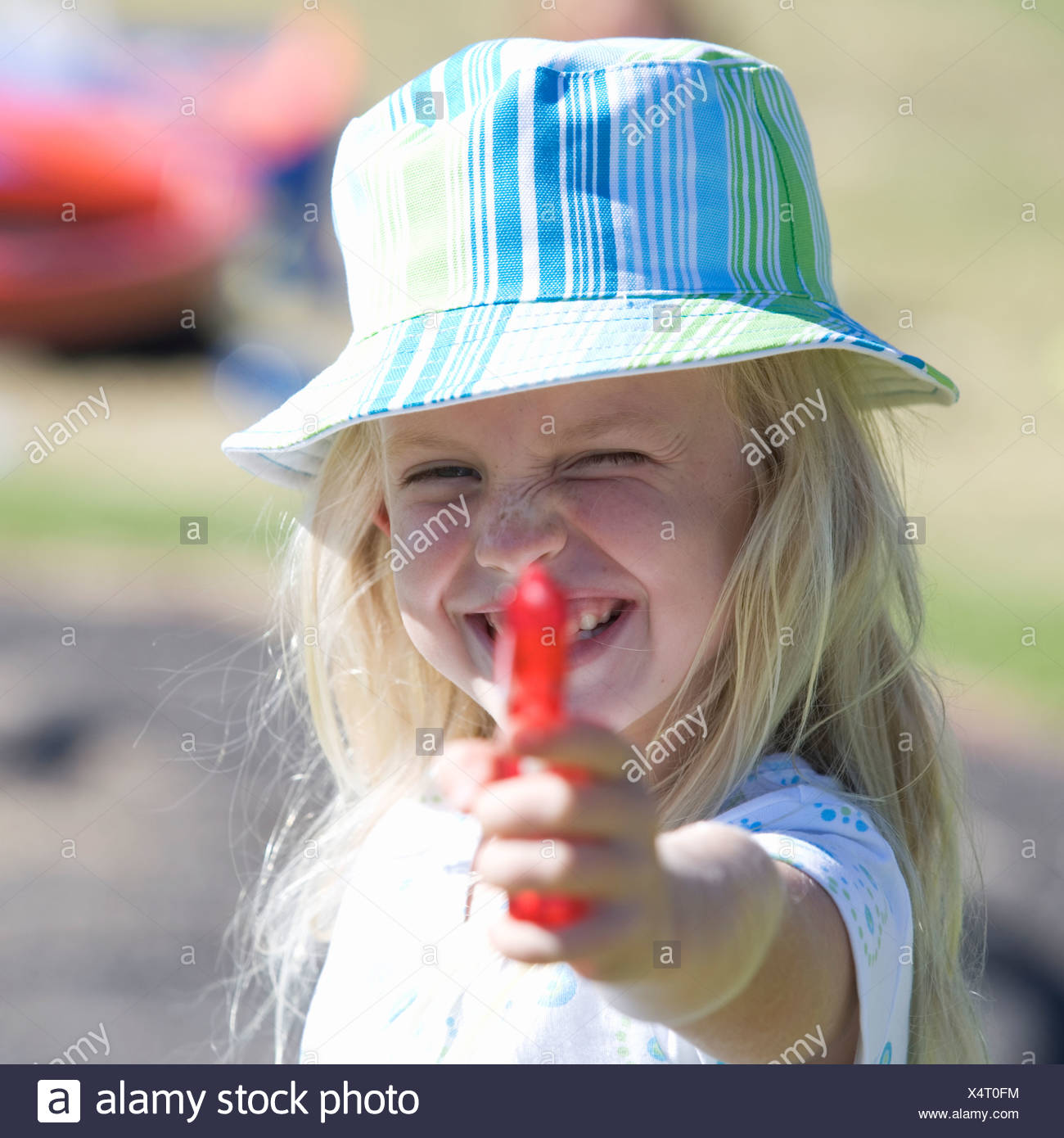 A young girl with a water pistol - Stock Image