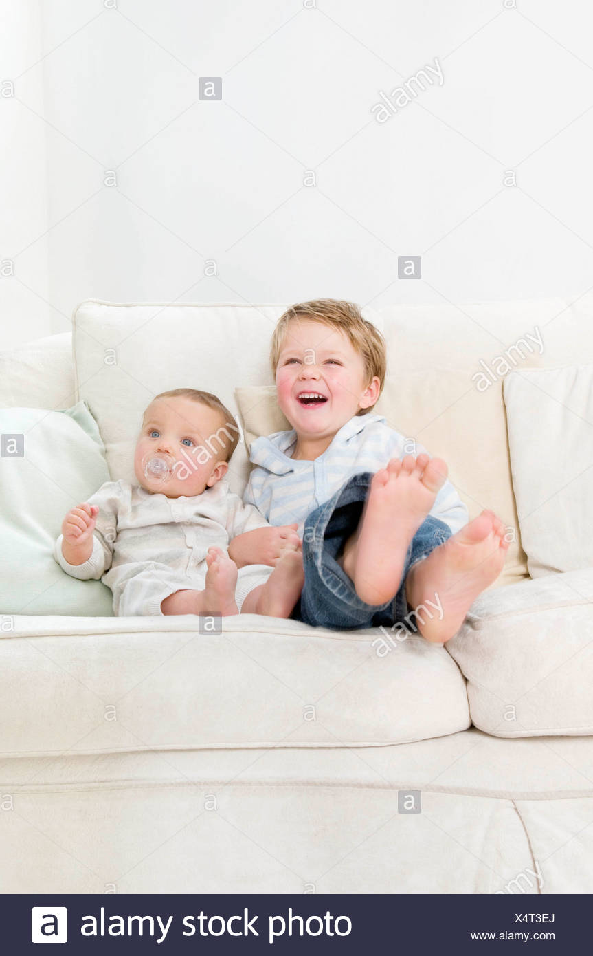 Brothers sitting together on a sofa - Stock Image