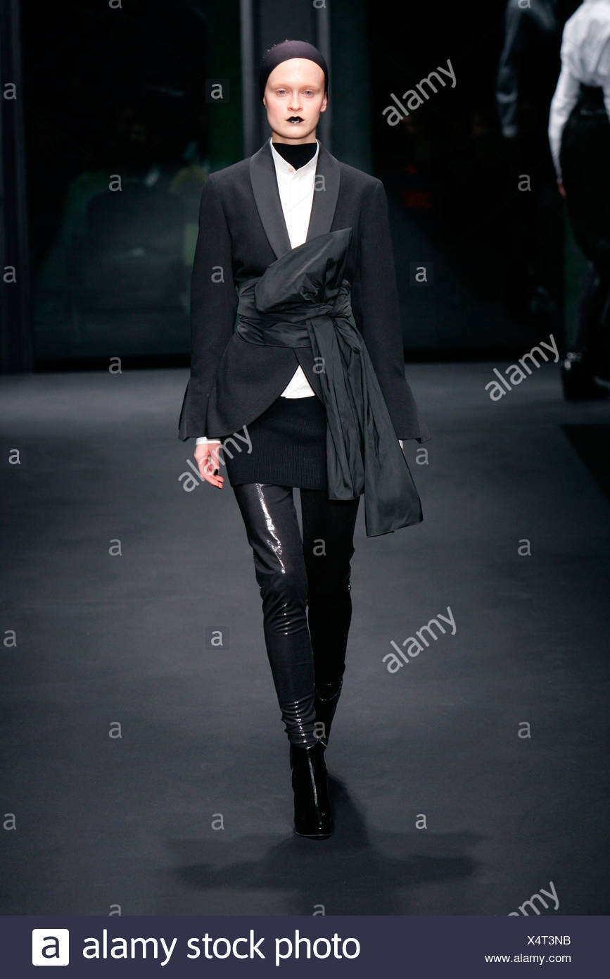 All black dinner jacket big tie bow belt, white shirt short skirt over skinny pants, suede ankle boots, headband and black - Stock Image