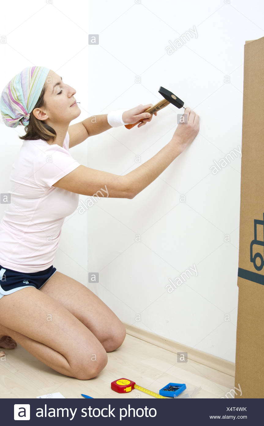 Young Woman Hammering A Nail In The Wall Nail In Her Mouth Model